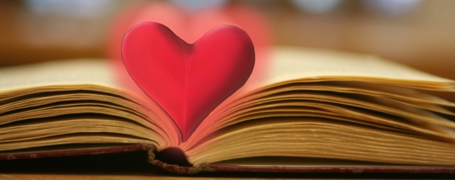 A book laying open with its pages folded in to make a heart shape. There is a image of a heart over the folded pages.
