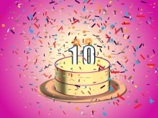 A yellow and pink birthday cake with lit #10 candles. The cake is showered in confetti.