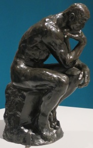 "Image of the sculpture ""The Thinker"". It's a man sitting on a stone block. He is leaning on his right arm and his left arm rests on his left knee."