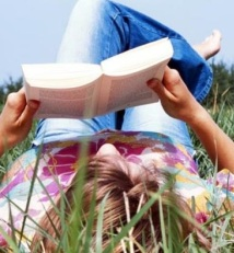 A girl is relaxing in a grassy field enjoying a book.