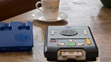 A photo of a talking book player with a digital cartridge inserted. The cartridge case is next to the player and there is a cup of coffee in the background.